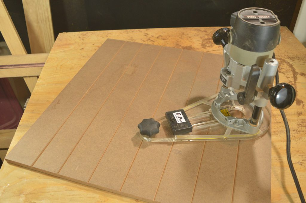 A wood panel and MLCS's featured product, the OnPoint Laser Guided Router Base Plate.